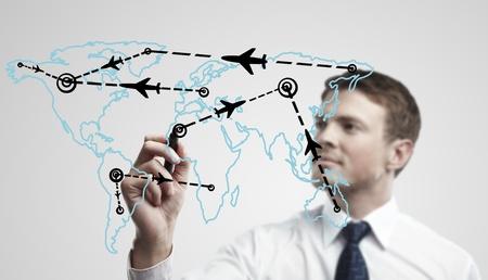 INTERNATIONAL BUSINESS: Joven hombre de negocios dibujar un avión rutas en el mapa mundial. El hombre de dibujo mapa del mundo con las aeronaves que vuelen en una ventana de cristal. La metáfora de los viajes aéreos internacionales en todo el mundo, los viajes a cualquier parte del planeta Tierra y la carga de trabajo del tráfico aéreo Foto de archivo