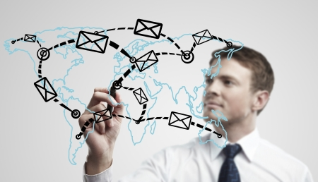 Young business man drawing a global network with envelopes on world map. Man drawing  E-mail Icon on a glass window.  The metaphor of international communication around the world. On a gray background. photo