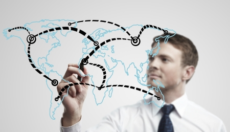 Young business man drawing a global network or globalization concept on world map.  Man drawing internet diagram or business connection on a glass window. On a gray background. photo