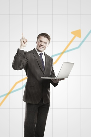 Happy young business man with laptop showing thumbs up.  On a gray background with rising arrow, representing business growth Stock Photo - 11499084