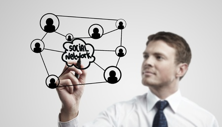 Young business man drawing a social network or globalization concept.  Man drawing a global network on a glass window. On a gray background. Stock Photo - 11788906