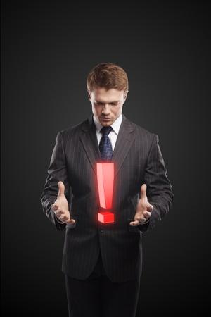 poner atencion: Joven empresario con un signo de exclamación en sus manos. En un fondo negro Foto de archivo