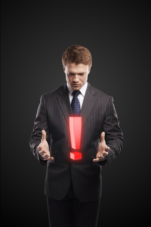 unsolvable:  Young  businessman with an exclamation mark on his hands. On a black background