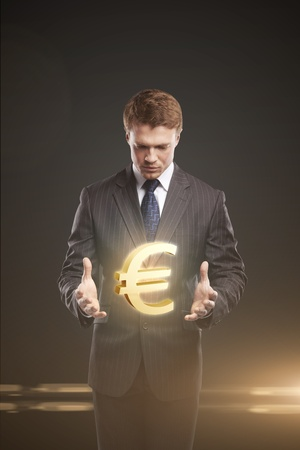 Young  businessman chooses a Gold Euro Sign. On a black background photo
