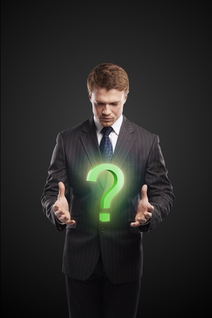 unanswered: Young  businessman with a question mark on his hands. On a black background