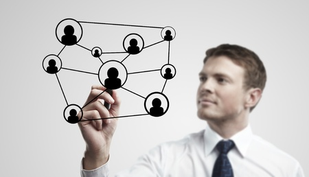 Young business man drawing a social network or globalization concept.  Man drawing a global network on a glass window. On a gray background. photo