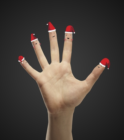 winter theater: Fingers dressed in Santa-Claus red-white hats. Group of happy finger smileys  representing a social network.  On a black background Stock Photo