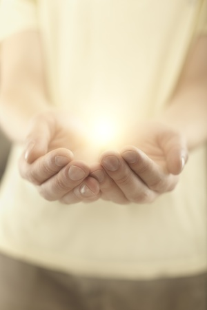 orando manos: Manos de los hombres la celebraci�n de los rayos de luz que brilla intensamente. Energ�a m�gica en las manos. Enfoque suave Foto de archivo