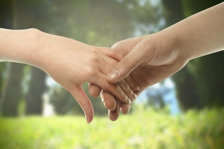 couples outdoors: Couple hands closed together outdoors. Hand-in-hand. Couple love on background of nature Stock Photo