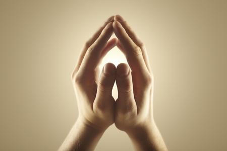 manos abiertas: Manos de los hombres la celebraci�n de los rayos de luz que brilla intensamente. Energ�a m�gica en las manos. El enfoque suave Foto de archivo