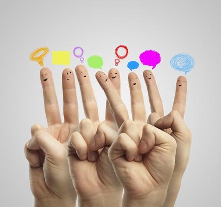 apoyo social: Feliz grupo de smileys dedos con el signo de charla social y bocadillos. Los dedos representan a una red social.