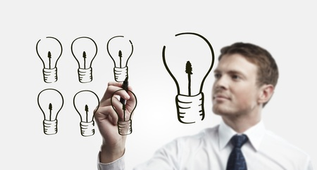 coming up with: Young business man drawing many small light bulbs equal a big one  Man coming up with an idea on a glass screen with black marker  On a gray background