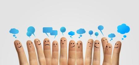 社会チャット記号とスピーチ泡社会的ネットワークを表す指と指スマイリーの幸せなグループ 写真素材