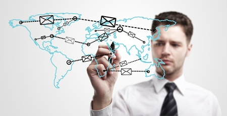 Young business man drawing a global network with envelopes on world map  Man drawing  E-mail Icon on a glass window   The metaphor of international communication around the world  On a gray background  photo