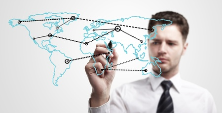 a window on the world: Young business man drawing a global network or globalization concept on world map   Man drawing internet diagram or business connection on a glass window  On a gray background