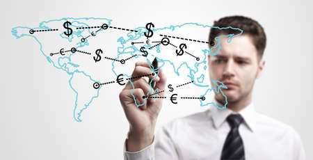 Young business man drawing a global network with Dollar Signs on world map   The metaphor of international communication around the world  On a gray background  Stock Photo - 13366203