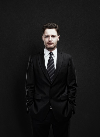 serious guy: Portrait of a young businessman standing with his hands in the pockets  Young handsome man  looking confident  On a black  background