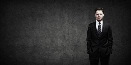 serious businessman: Portrait of a young businessman with place for your text  Man standing with his hands in the pockets  Young handsome man  looking confident  On a  gray background