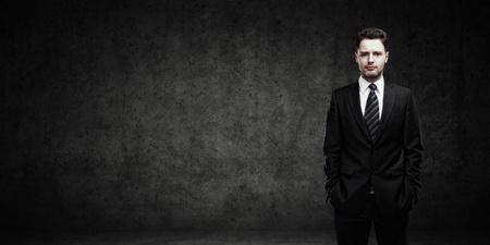 Porträt eines jungen Geschäftsmann mit Platz für Ihren Text Man Standing mit den Händen in den Taschen junger stattlicher Mann sucht Auf einem schwarzen Hintergrund zuversichtlich