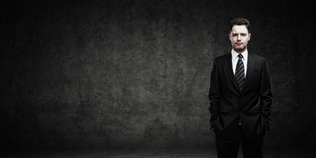 Portrait of a young businessman with place for your text  Man standing with his hands in the pockets  Young handsome man  looking confident  On a black background