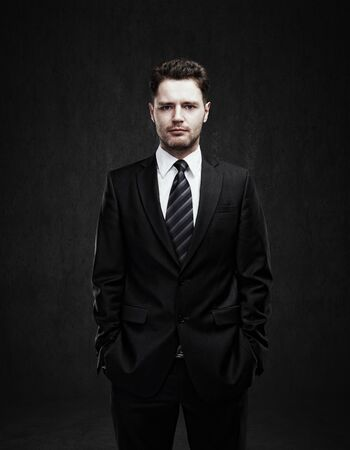 businessman standing: Portrait of a young businessman standing with his hands in the pockets  Young handsome man  looking confident  On a black  background