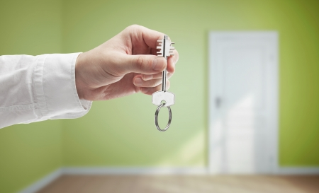 key in hand on background of light green room Stock Photo - 13999432