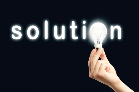 solutions: light bulb in hand and word solution on black background Stock Photo