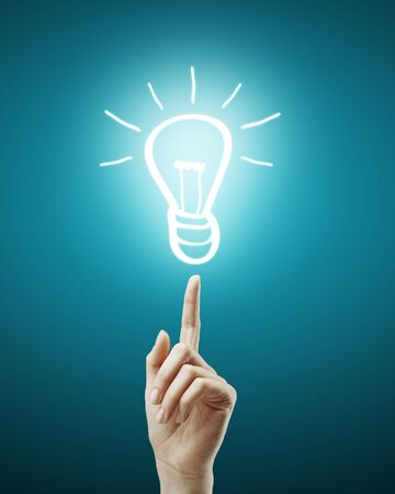 hand points to drawing  light bulb Stock Photo - 14130174