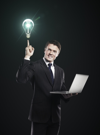 businessman with laptop in hand points to the light bulb photo