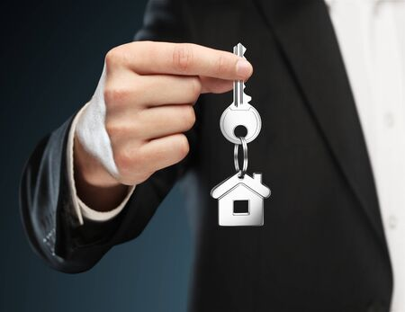 man gives keys to house on a blue background Stock Photo - 14206003