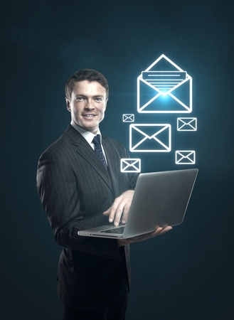 send email: businessman with a laptop in hand and mail symbol