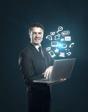 businessman with a laptop in hand and a sign of social networks photo