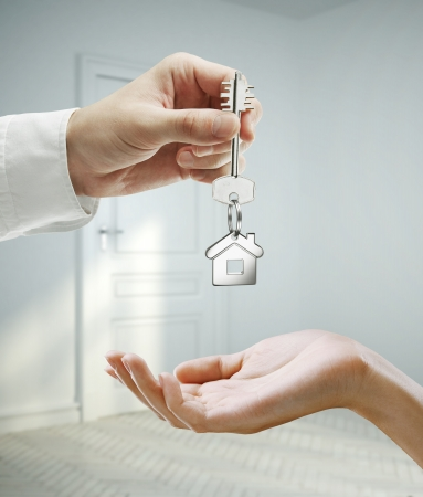passing keys against backdrop of gray room photo