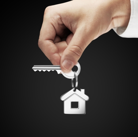 house in hand: key chain with key in hand man Stock Photo