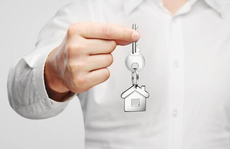 giving house key with house shaped keychain photo