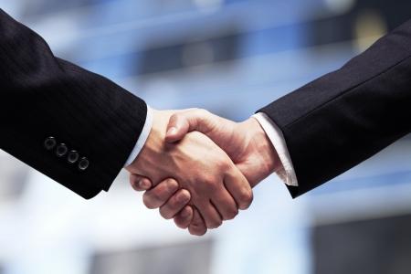 dandose la mano: hombres de negocios d�ndose la mano en el fondo de los rascacielos Foto de archivo