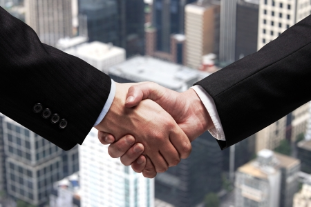 businessmen shaking hands on background of city photo