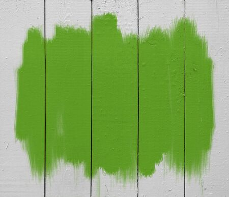 green paint brush strokes on white wooden plank photo