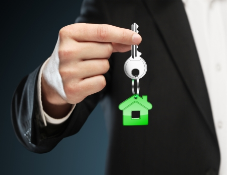 thumb keys: green key chain with key in hand  businessman