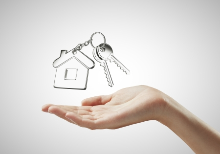 house in hand: key with  key chain on hand on white background Stock Photo