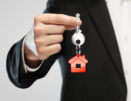 thumb keys: red key chain with key in hand  businessman Stock Photo