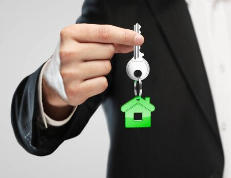 real man: green key chain with key in hand  businessman