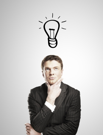 enlightenment: pensive man with a drawing lamps over his head Stock Photo