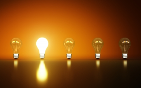 light bulbs stand in rows one glows on a orange background Stock Photo - 14641524