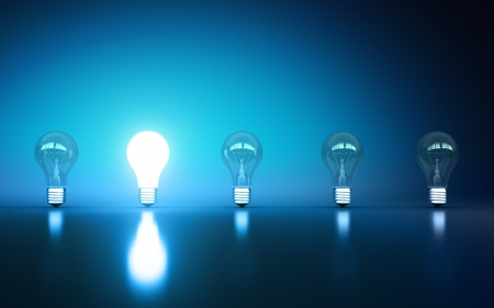 light bulbs stand in rows one glows on a blue background Stock Photo - 14641525