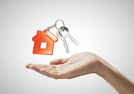 hands holding house: key with  red key chain in hand on white background Stock Photo