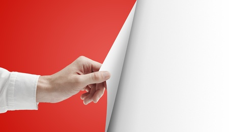 paper curl: men hand turns red page on white background Stock Photo