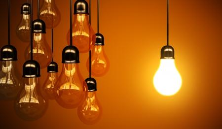 strom: Idee Konzept mit Gl�hbirnen auf einem orangefarbenen Hintergrund Lizenzfreie Bilder