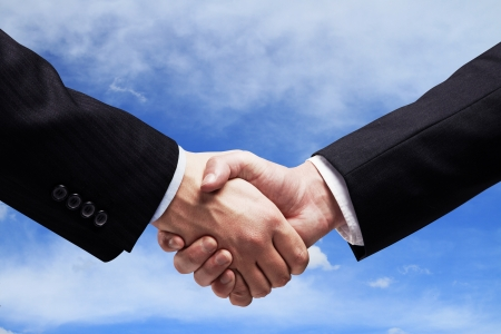 black handshake: handshake on  background of sky Stock Photo