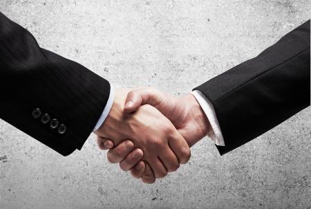saludo de manos: dos hombres de negocios d�ndose la mano sobre la pared de fondo